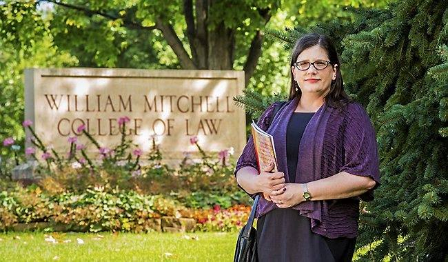 Image of Sarah Deer in front of the William MItchell College of Law sign